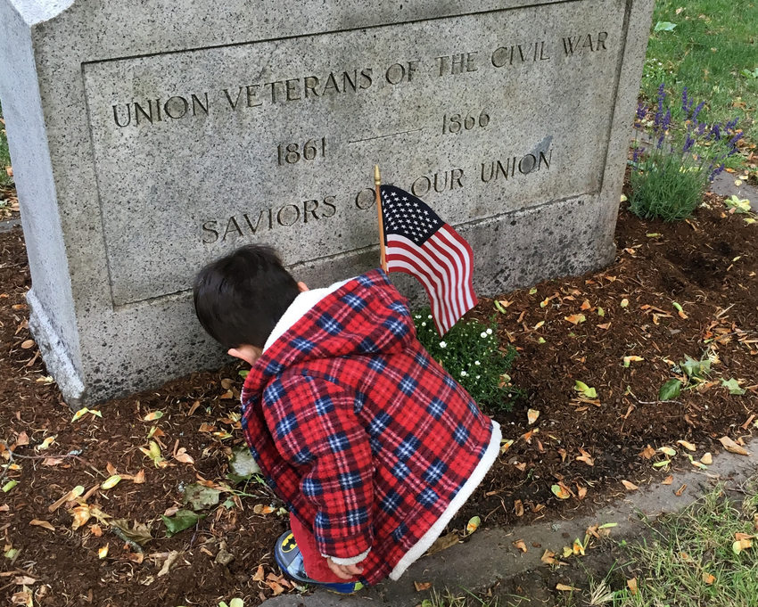 young child places American flag at the headstone of a grave site