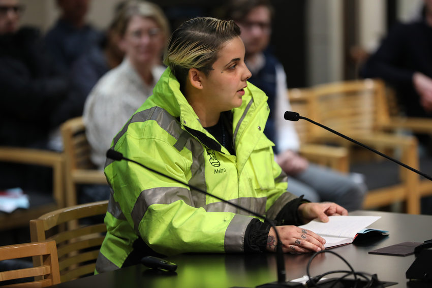a woman in a reflective work jacket sits at a table with a microphone
