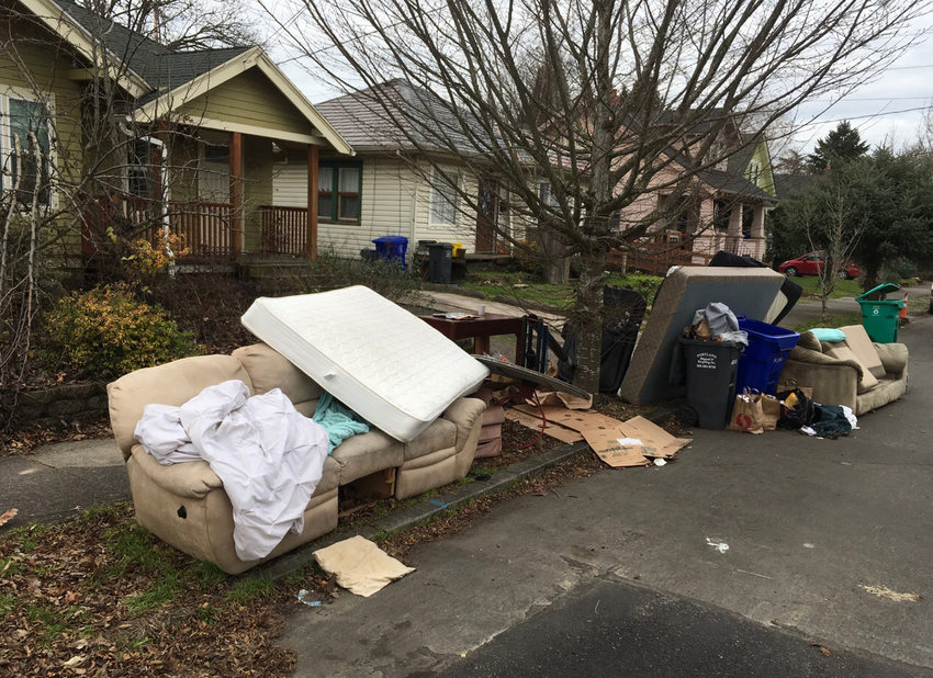 sofas,mattresses and trash on the curb in front of neighborhood homes