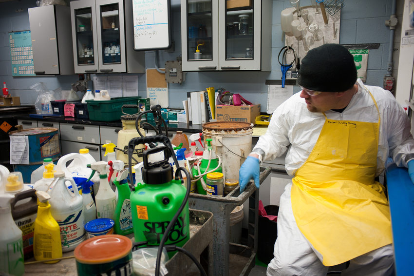 A metro hazardous waste worker looks at a number of dropped-off items