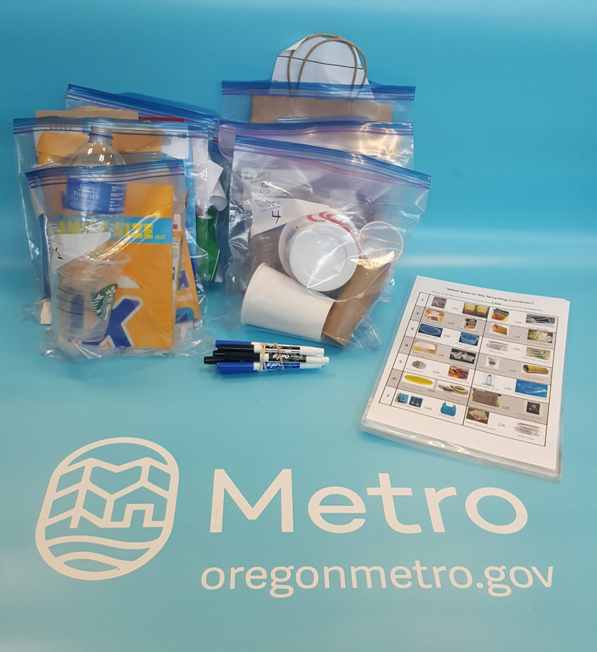 Curriculum and game props for the Recycling 101 education kit on a table