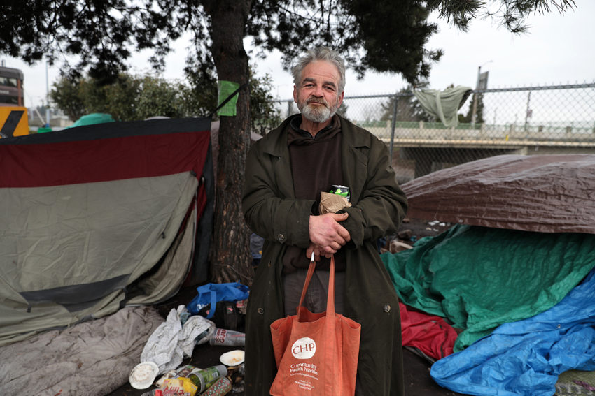 a man holding a tote bag stands in front of tents and tarps used as shelter for people experiencing homelessness