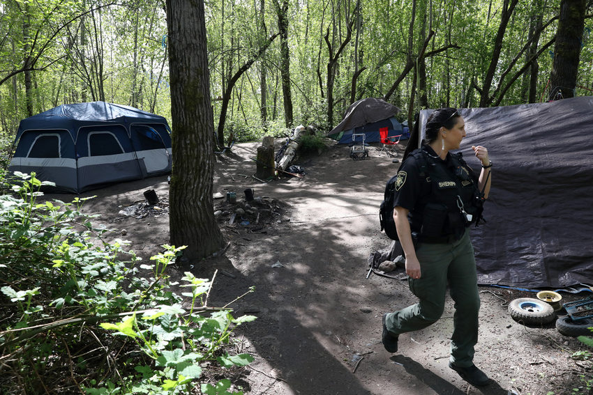 A sheriff's deputy walks through a tidy campsite with multiple tents.