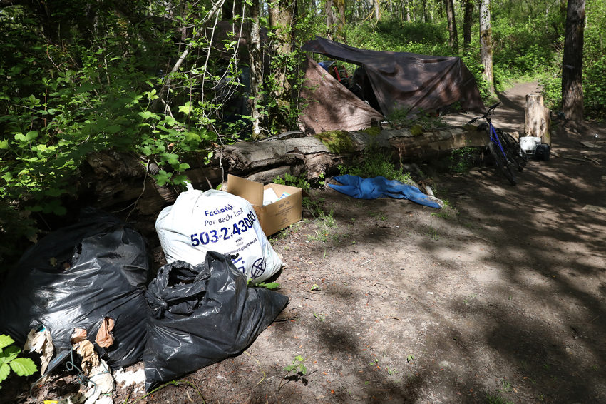 A full, white metro trash bag sits ready for collection next to other bagged trash in the woods