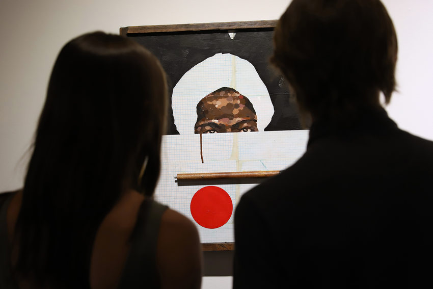 Two people look at a portrait of an African American man