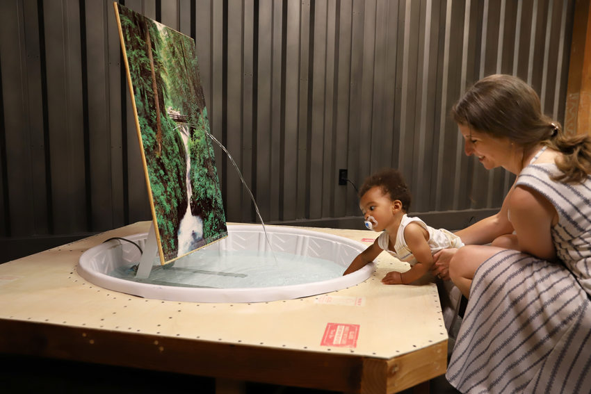 a woman holds a baby as it dips his hand into an art installation made out of a plastic wading pool
