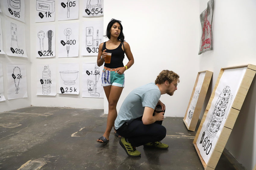a woman, with beer in hand, walks past a man crouching on the ground to look at a painting