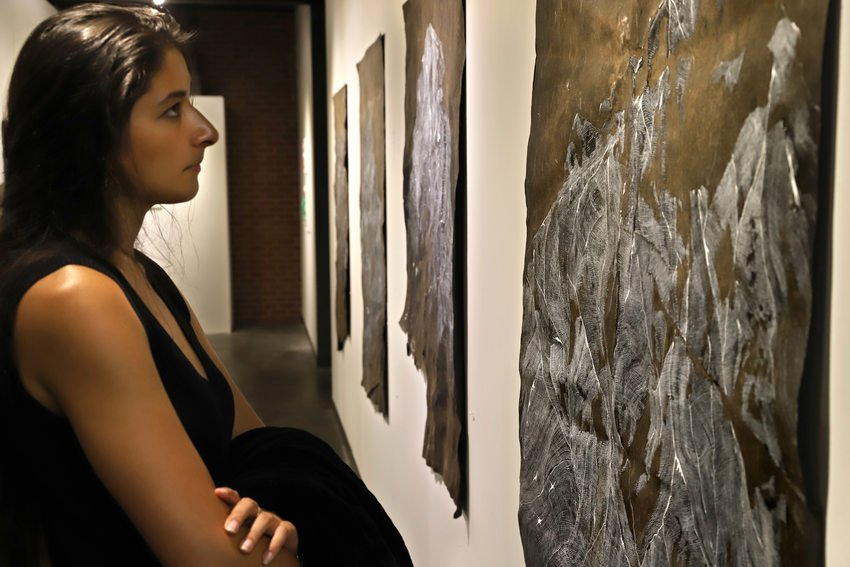 A woman gazes at an oversized landscape painting made from thousands of tiny lines