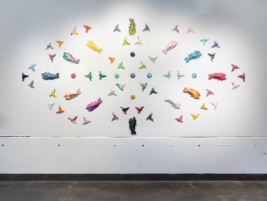 wall installation of assorted plastic shapes and creatures