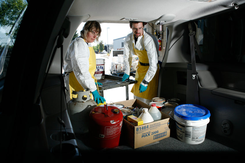 Hazardous Waste technicians removing hazardous waste from vehicle