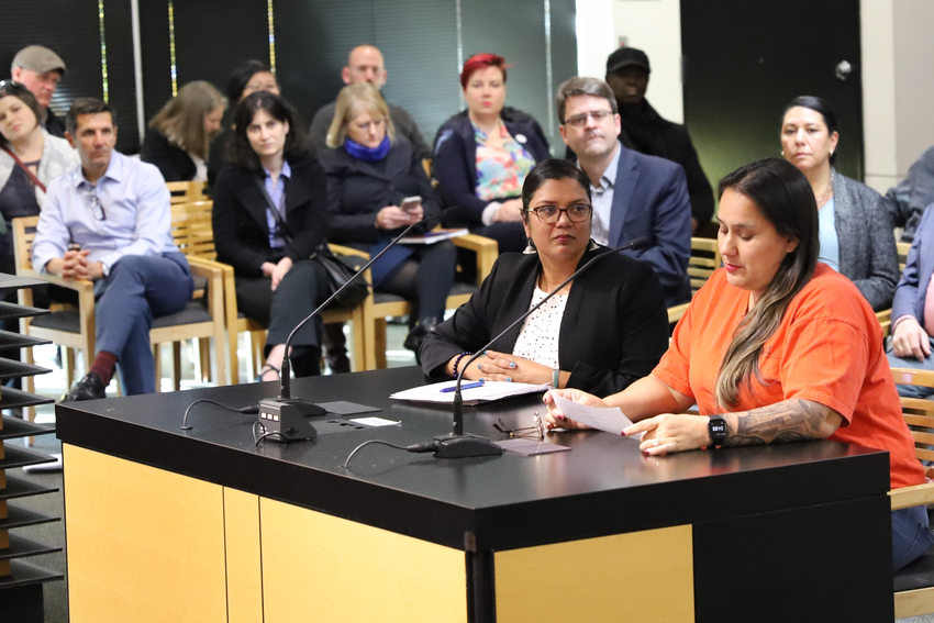 two women sit at a desk with microphones at a council chamber