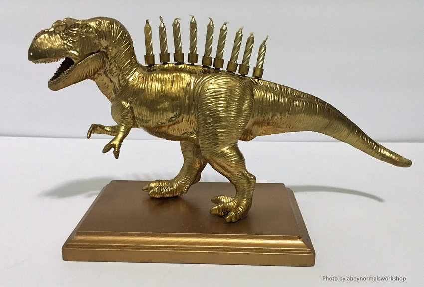 A child's toy dinosaur has been painted gold and turned into a menorah