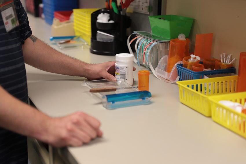 Pharmacy technician weighs pills to fill a prescription