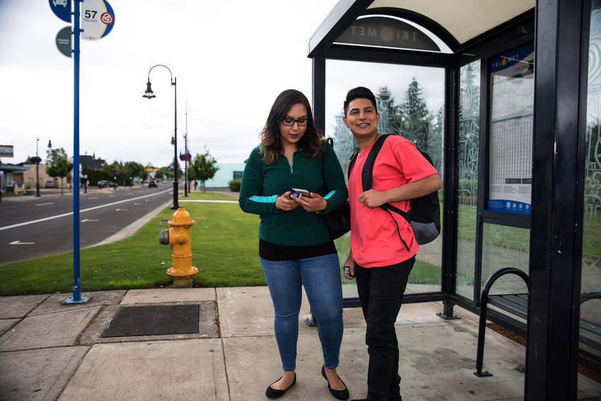 Two people, a young man and woman, wait at a bus stop.