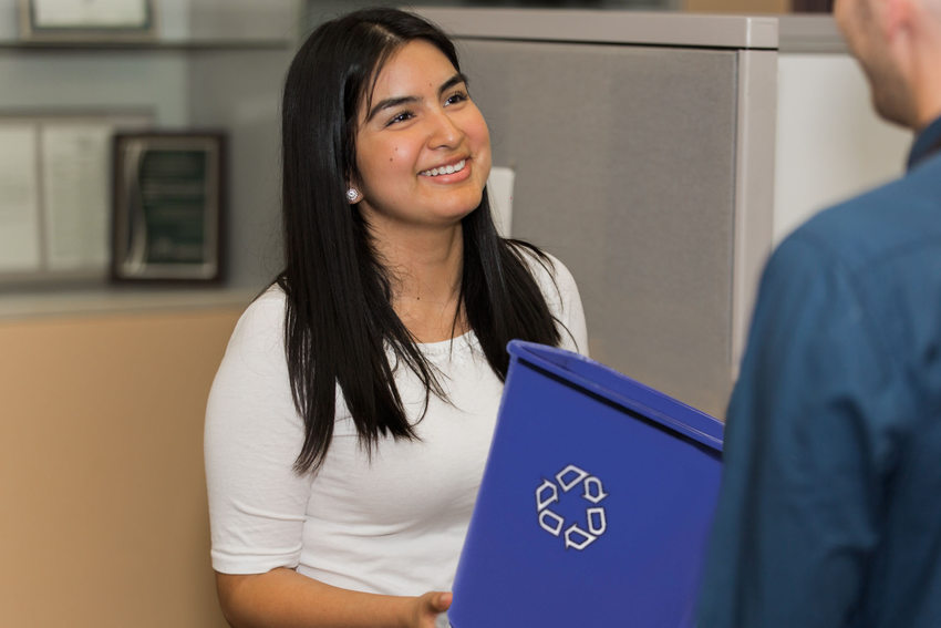 woman in the workplace with a blue recycle bin