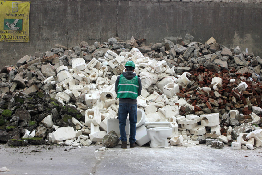 A GLEAN artist wearing a hardhat and safety gear stands before a pile of broken porcelain toilets at the transfer station