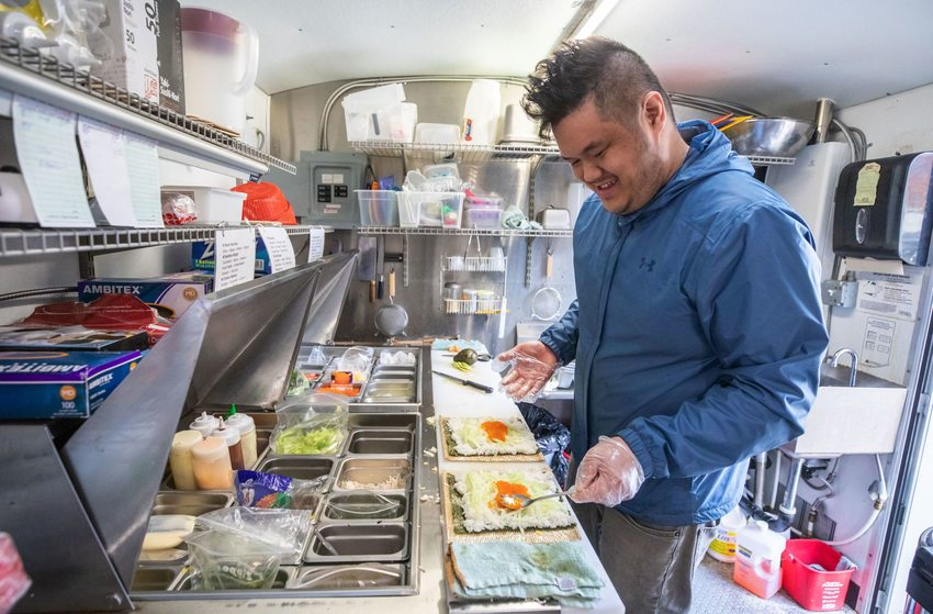 photo of Danny Chan, owner of Sumo Sushi food cart, making a sushi roll inside his food cart