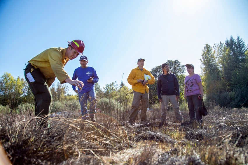 photo of Colby Drake, Greg Archuleta, Curt Zonick, Clifton and Christine Bruno inspecting a plant after a prescribed burn at Quamash Prairie Oct. 1, 2019