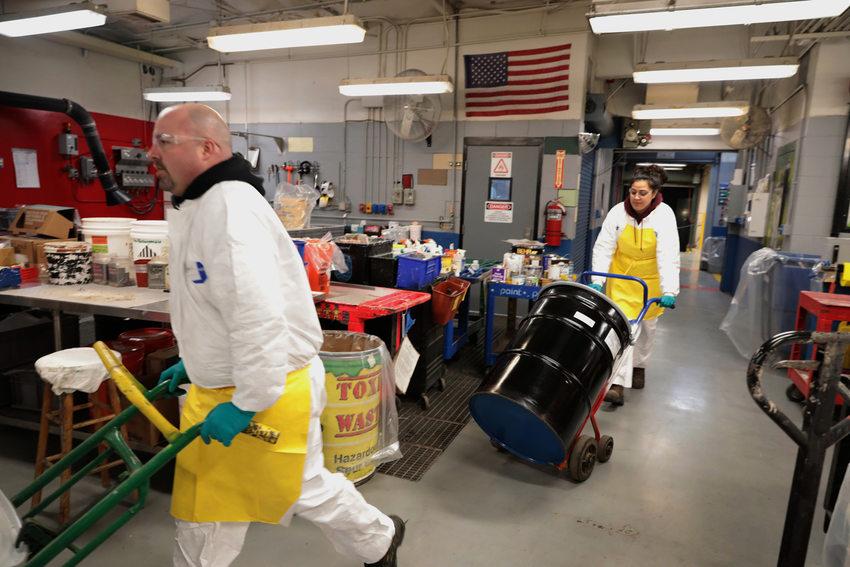 Annelise Tuitavuki moves a 55-gallon drum of hazardous waste