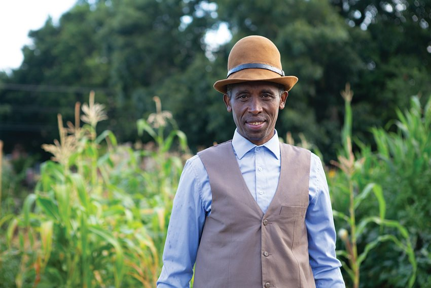 A Black man in a suit vest and leather brimmed hat stands in a garden.