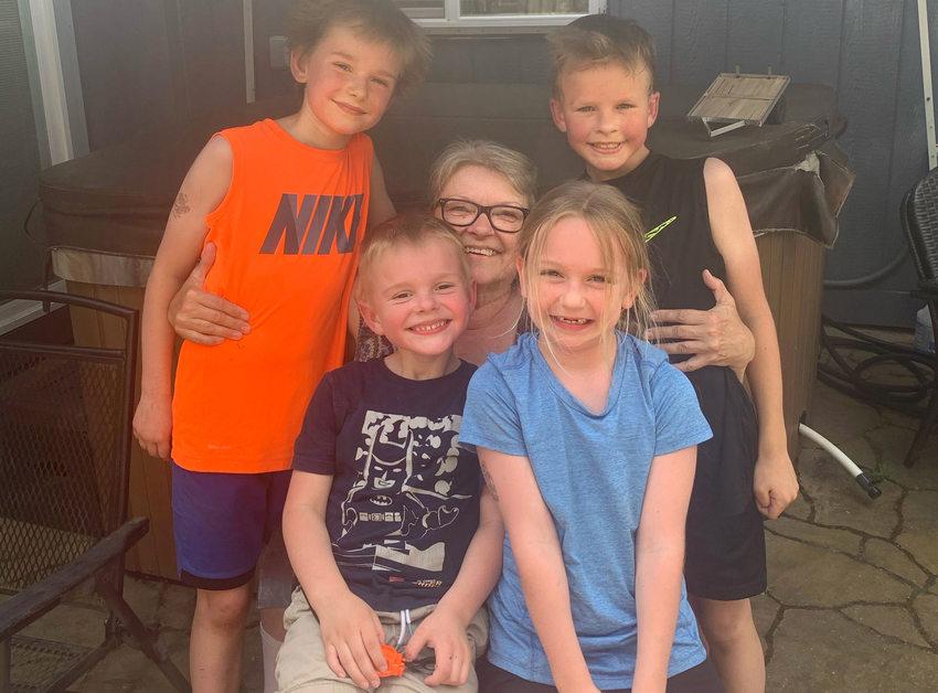 Una mujer sonriendo con sus cuatro nietos