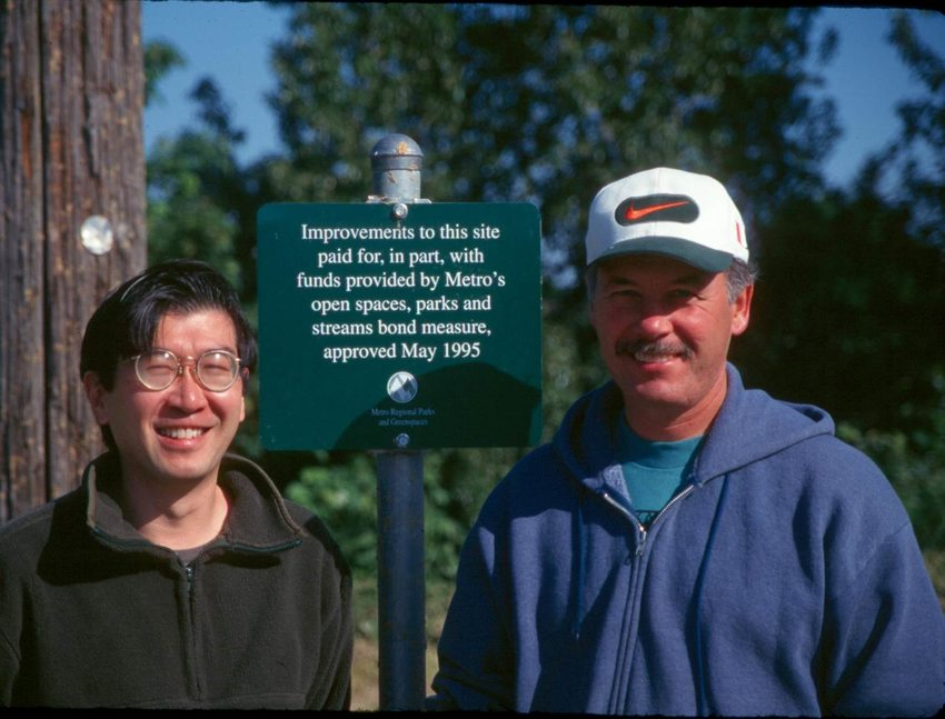 Mel Huie (left) and Jim Sjulin (right) standing next to a Metro sign about Metro bond approved in 1995.