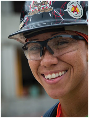 Headshot of a smiling construction worker wearing a hard hat and safety glasses