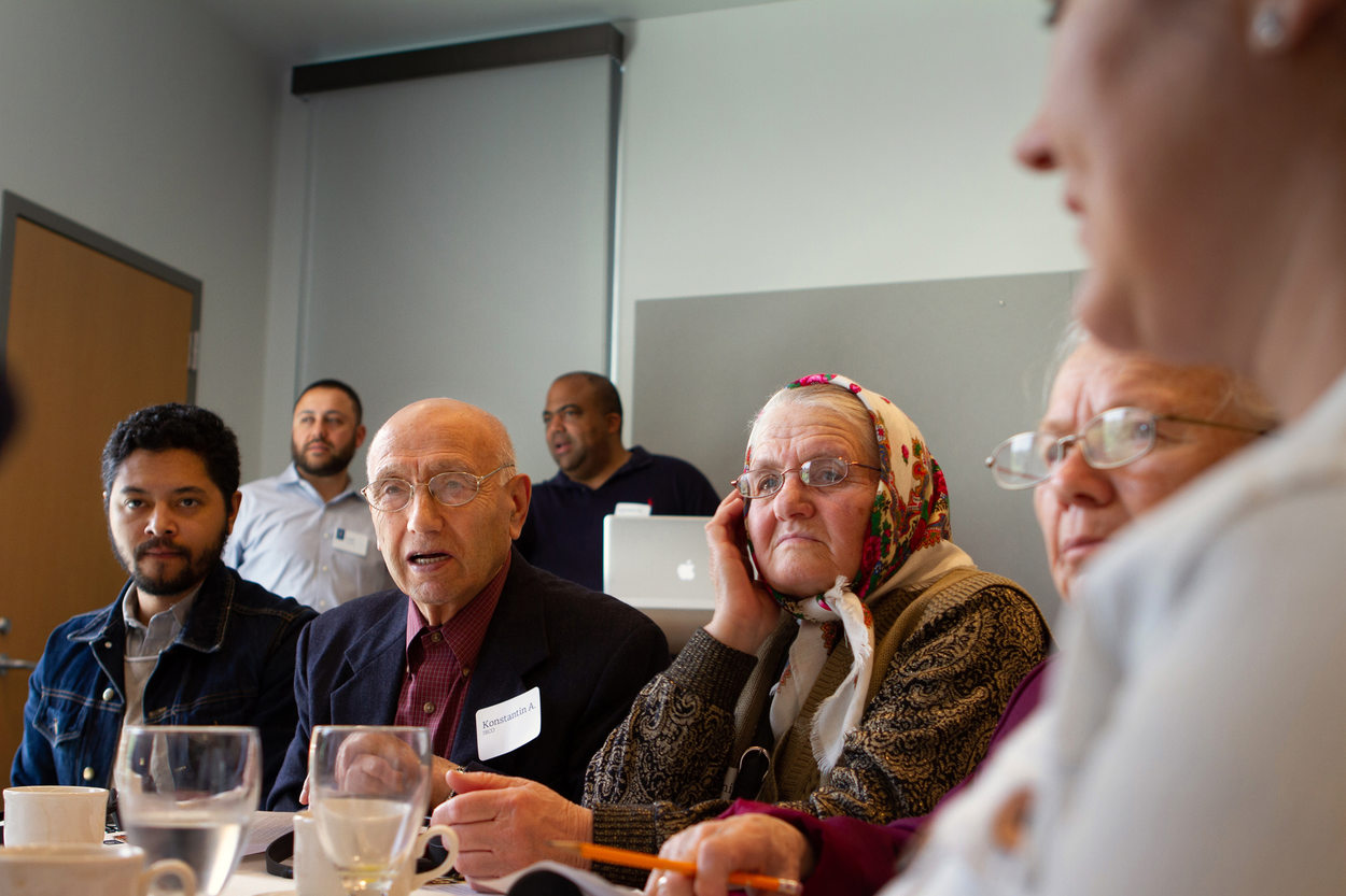 An elderly Russian speaker addresses the group at his table