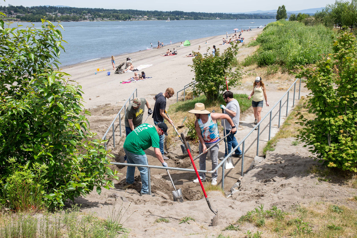 A group of volunteers using shovels to clean an access ramp of sand