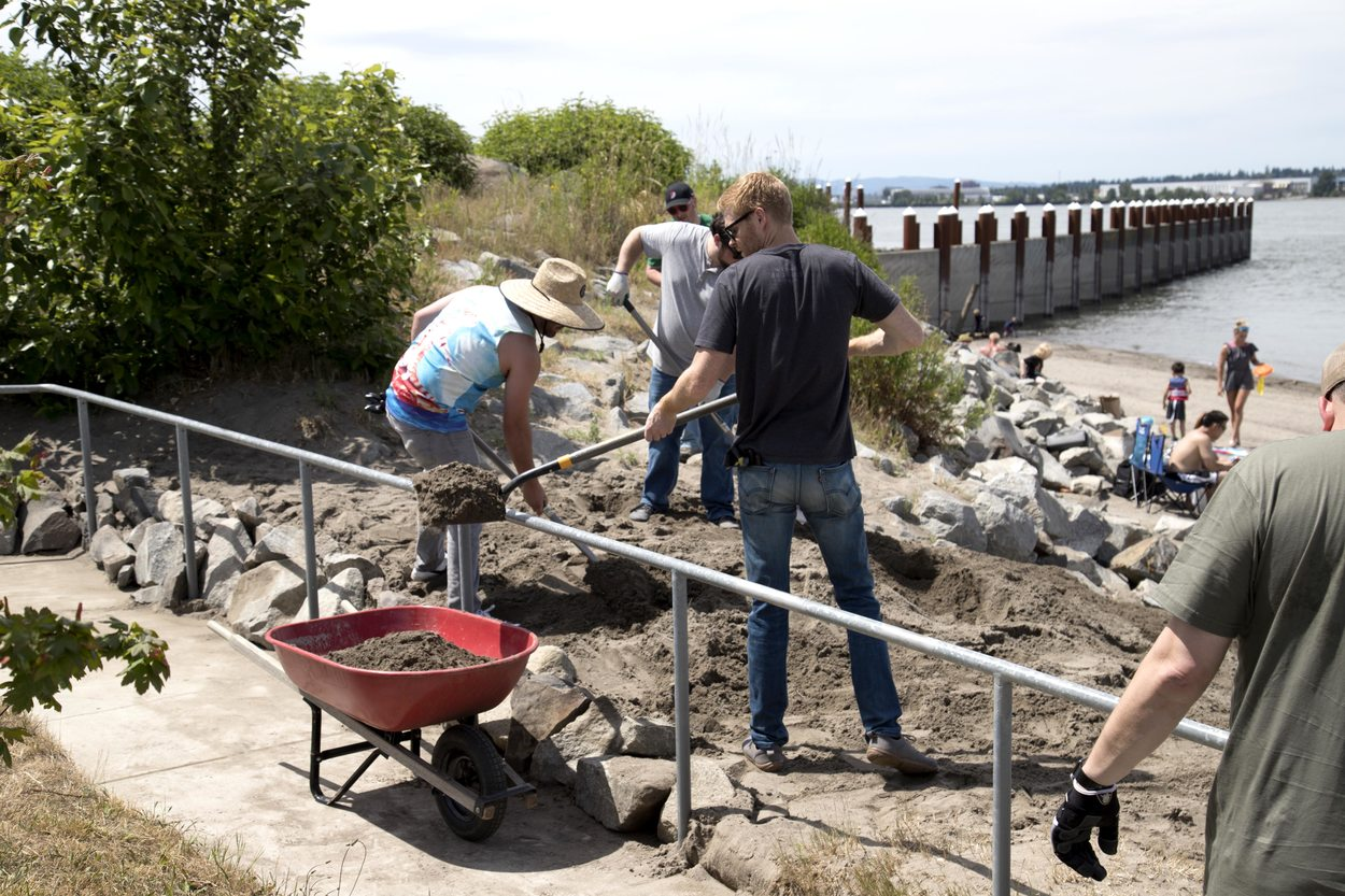 Two volunteers shovel sand into a wheelbarrow to clear an access ramp