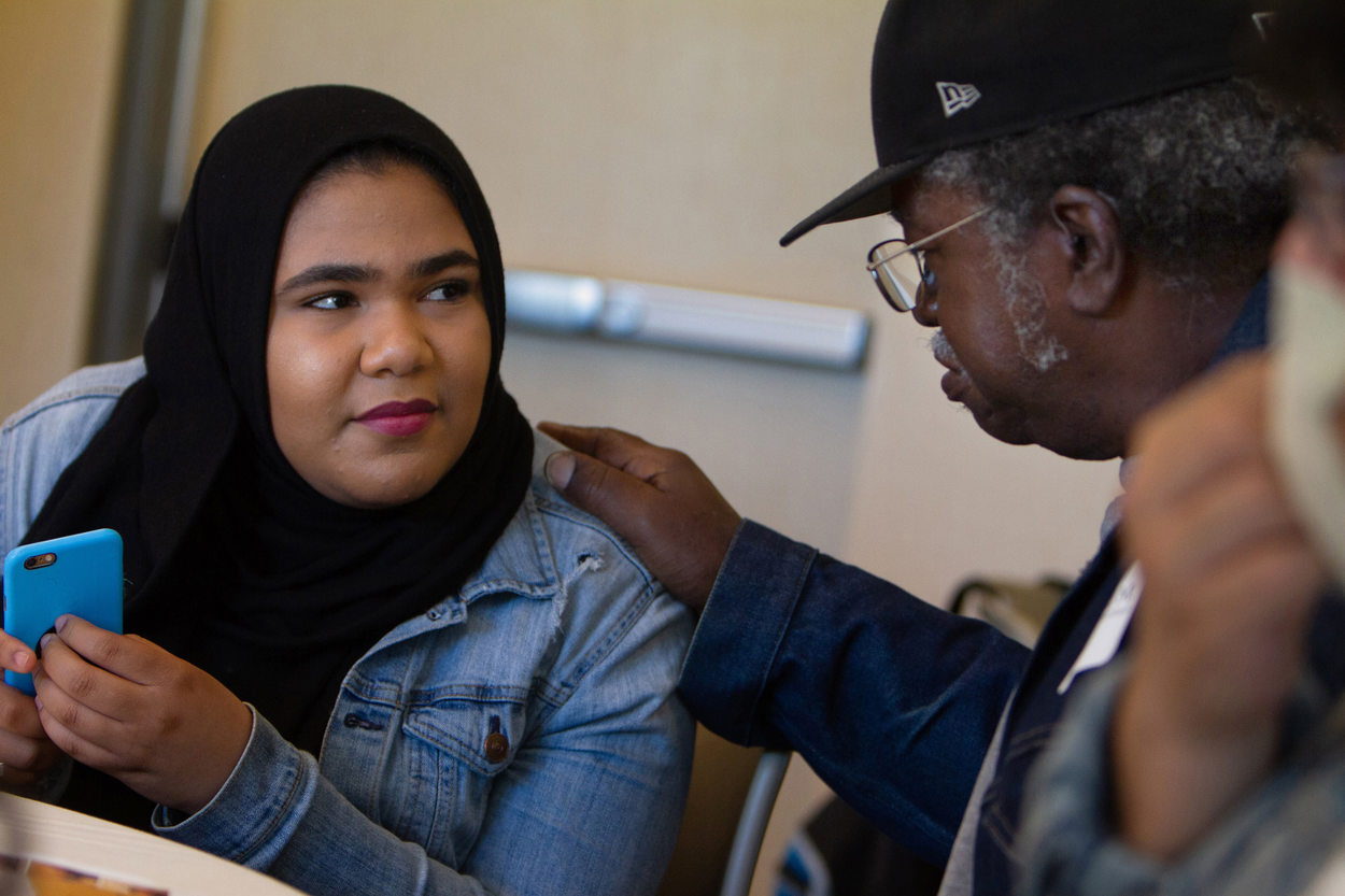 Elderly man leans in to talk with a young woman wearing a head scarf