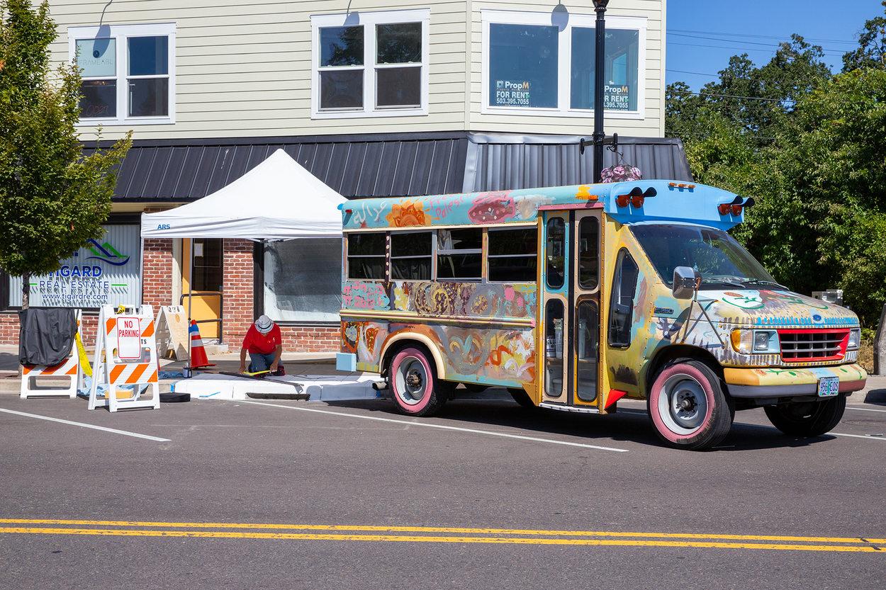 A man paints a mural beside a painted school bus