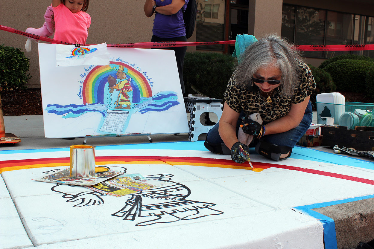 Artist Linda Dalal Sawaya paints a mural in Hillsboro, surrounded by onlookers
