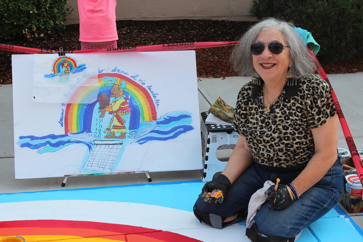 Artist Linda Dalal Sawaya smiles next to her placemaking mural