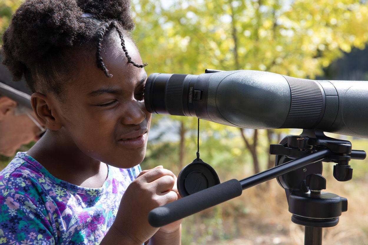 Nia Black, 7, looks through a telescope at Killin Wetlands Nature Park.