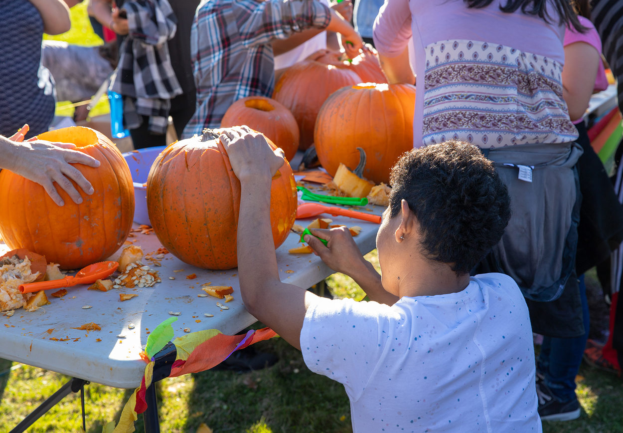 children carve pumpkins at a table while at an autumn harvest festival