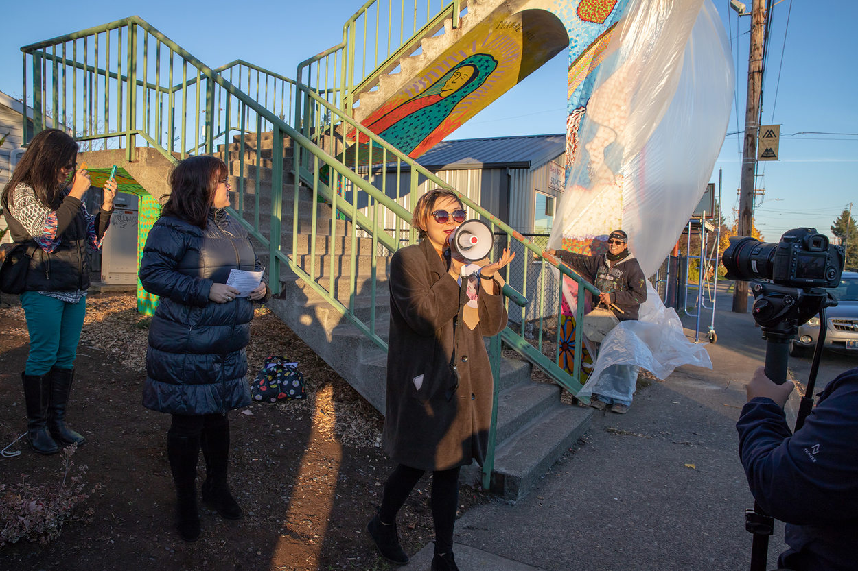 A woman speaks into a megaphone at the unveiling of a mural painting project