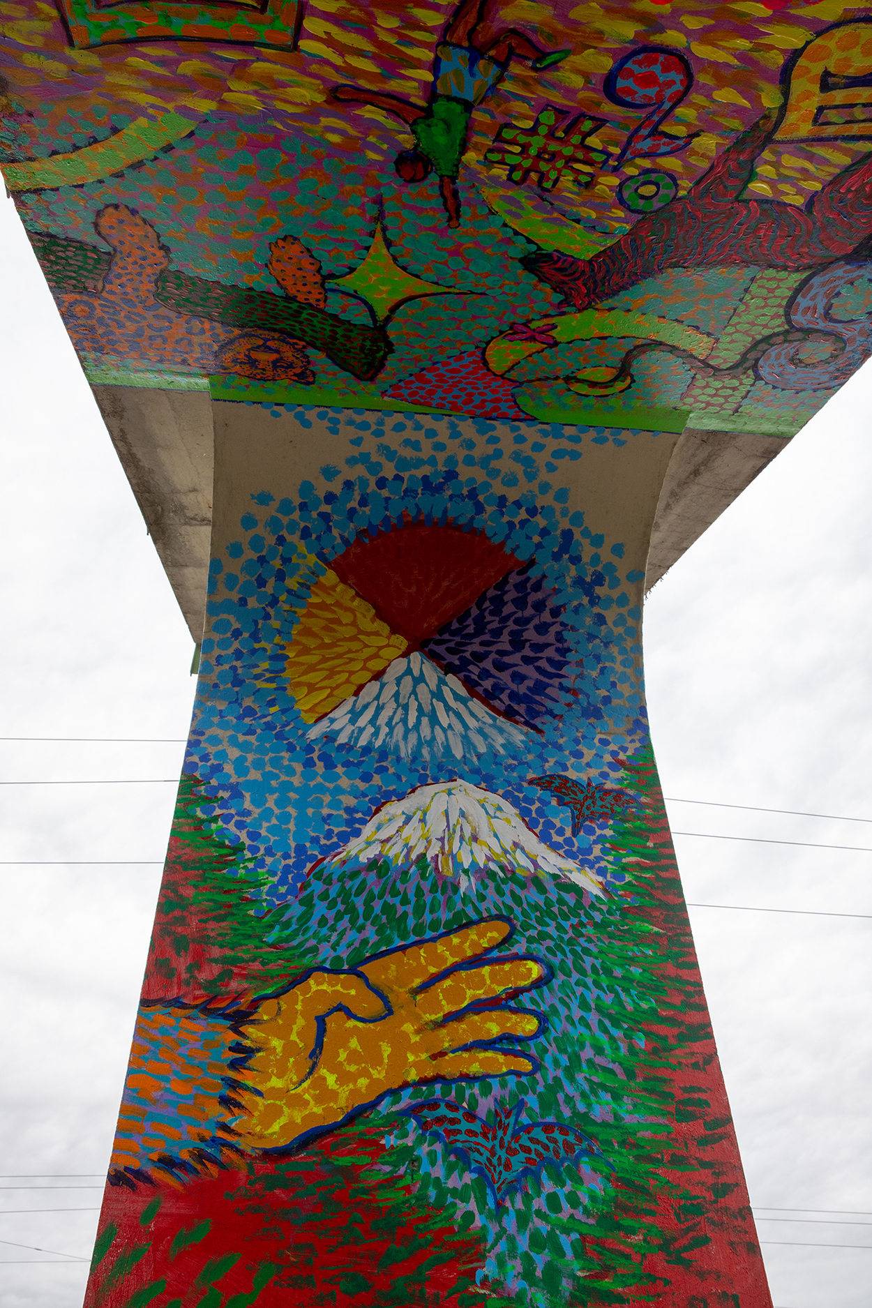 a closeup of a mural painted on a pedestrian bridge with a colorful medley of images
