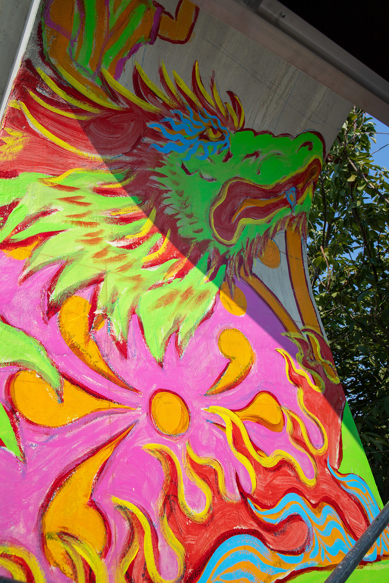 a close up of a mural painting on a pedestrian bridge showing a colorful lion