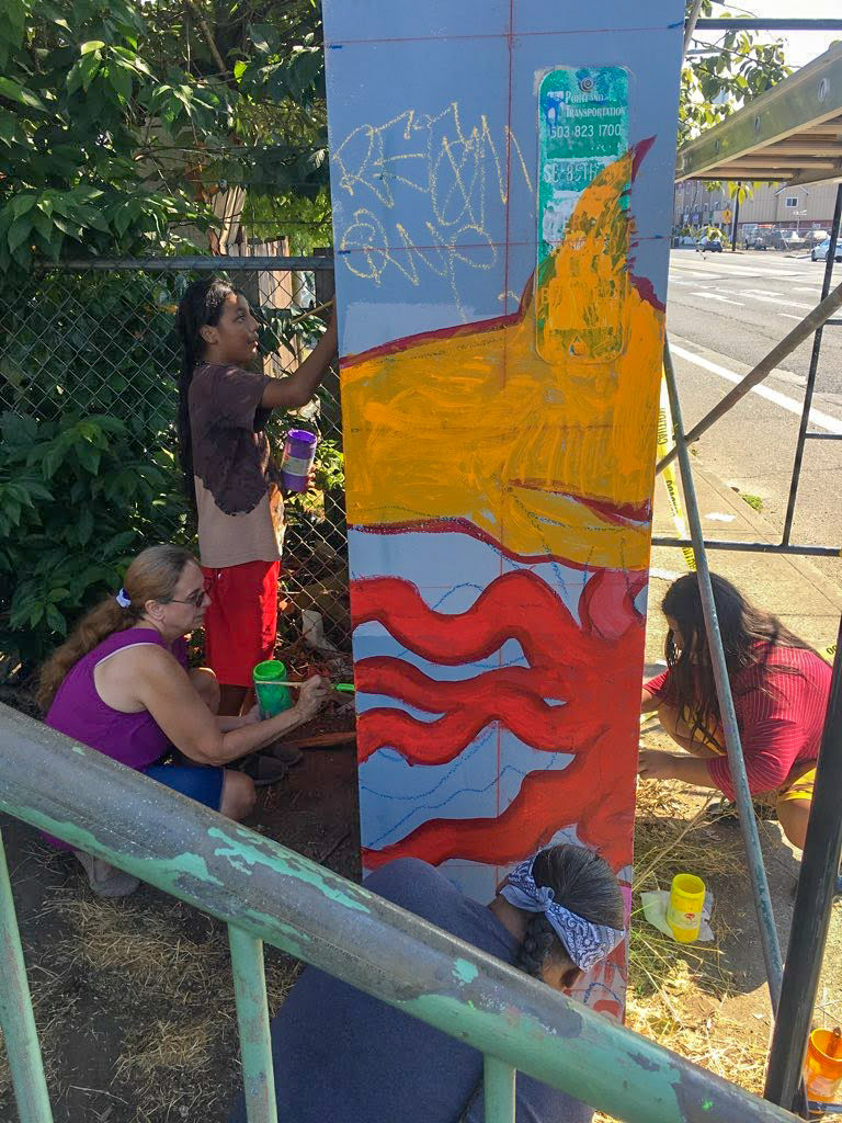 young kids and a woman paint along the column of a pedestrian bridge, where murals have been commissioned