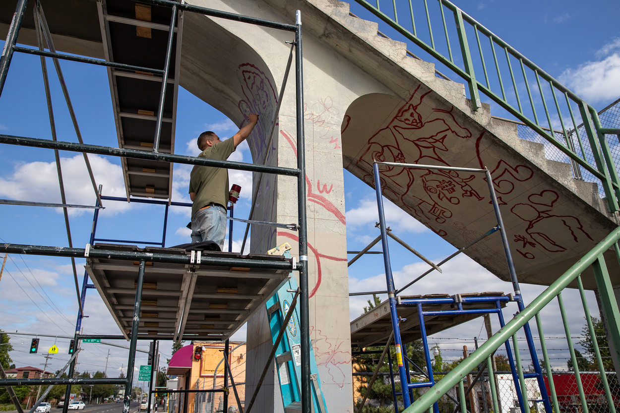 A young man paints the outline of images for a mural painting on a pedestrian bridge