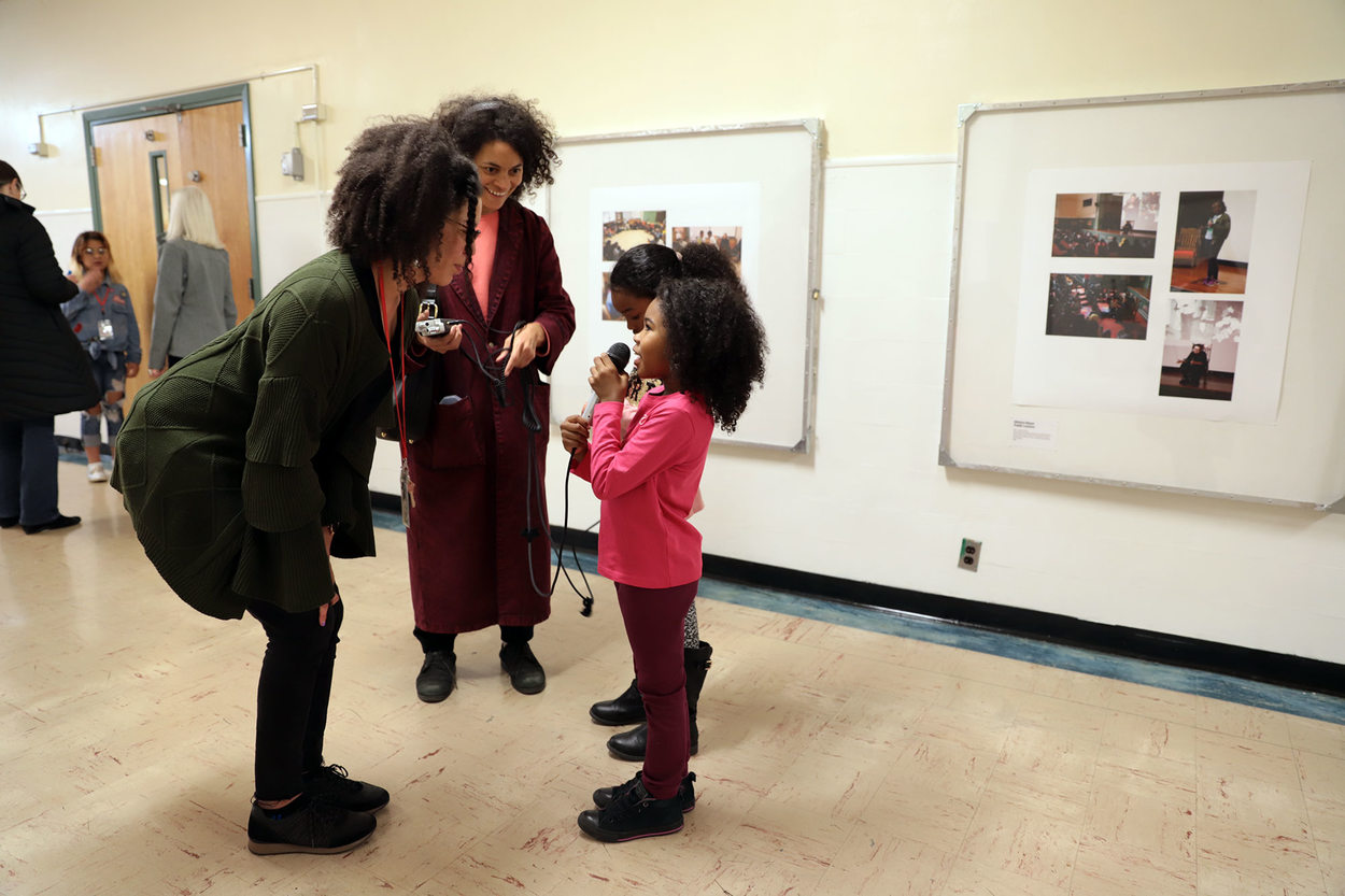 In a school hallway, a little girl speaks into a microphone as she interviews a woman, while her mentor stands by wearing headphones.