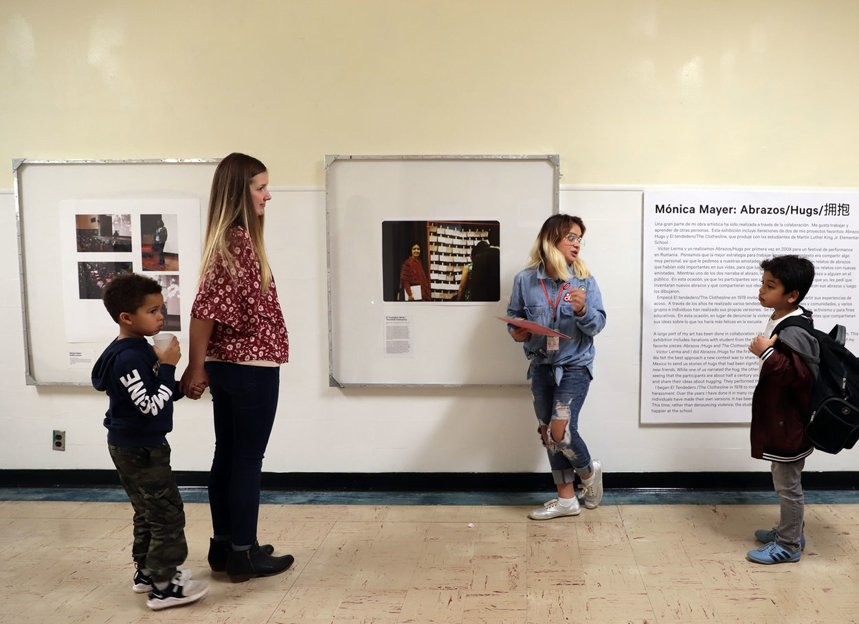 Children and a woman stand in a school hallway in front of encased works of art.