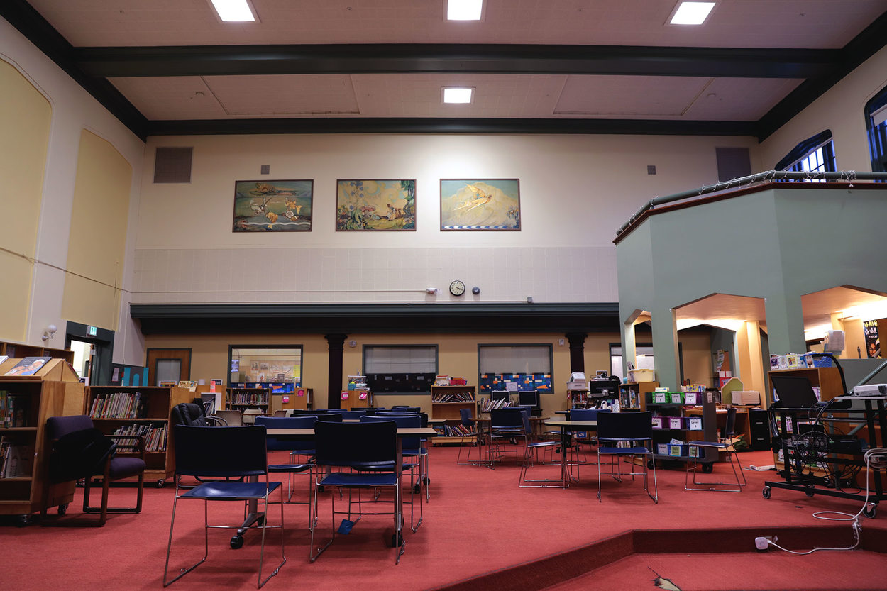 A school library with high ceilings. Three paintings hang on the wall 20 feet high - way above eye level even for an average adult.