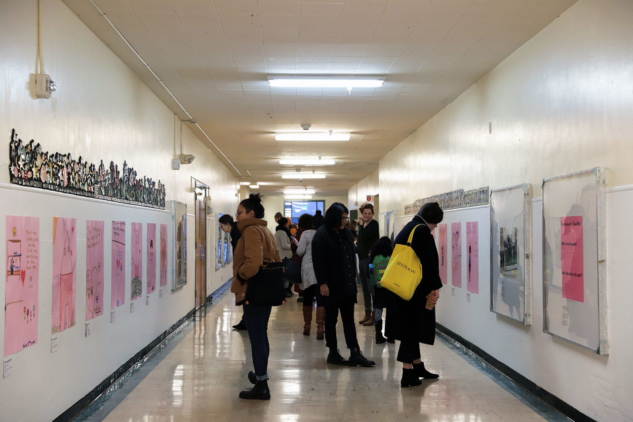 People look at art in a school hallway. The hallway is the main wing of an embedded contemporary art museum.