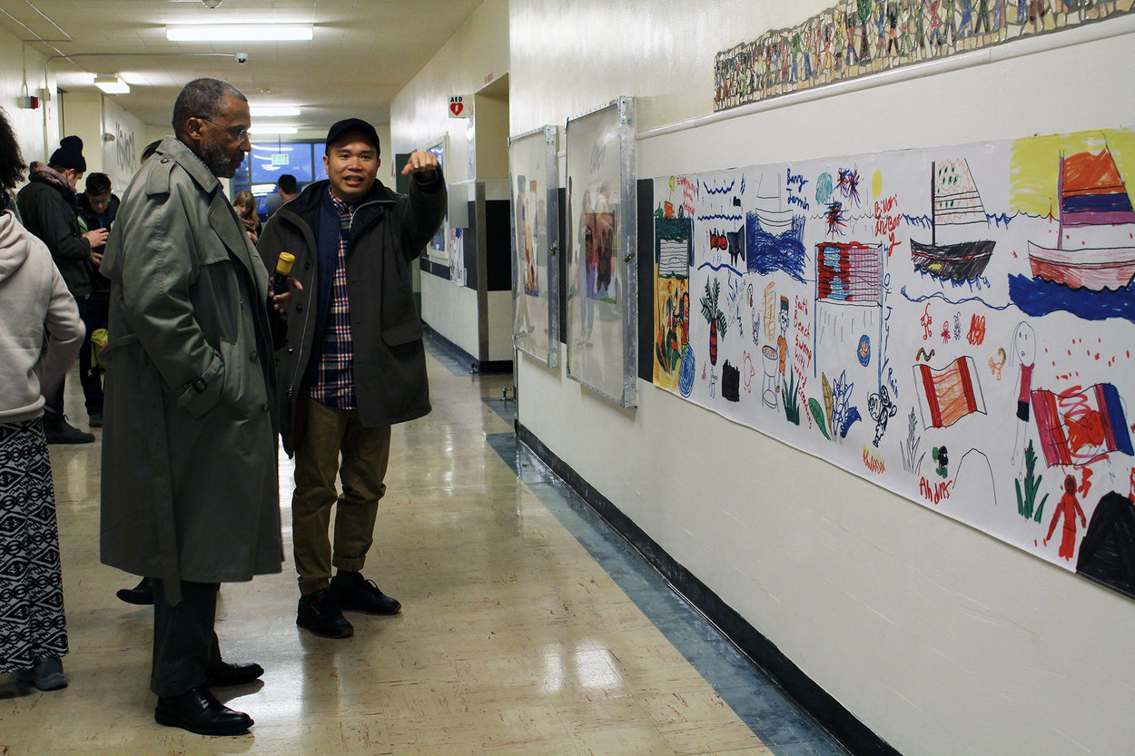 Two adults stand in the middle of a school hallway; one of them looks at art on the wall