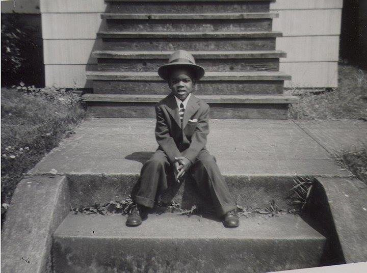 a portrait of a young boy wearing a suit as he sits on some steps in front of a house