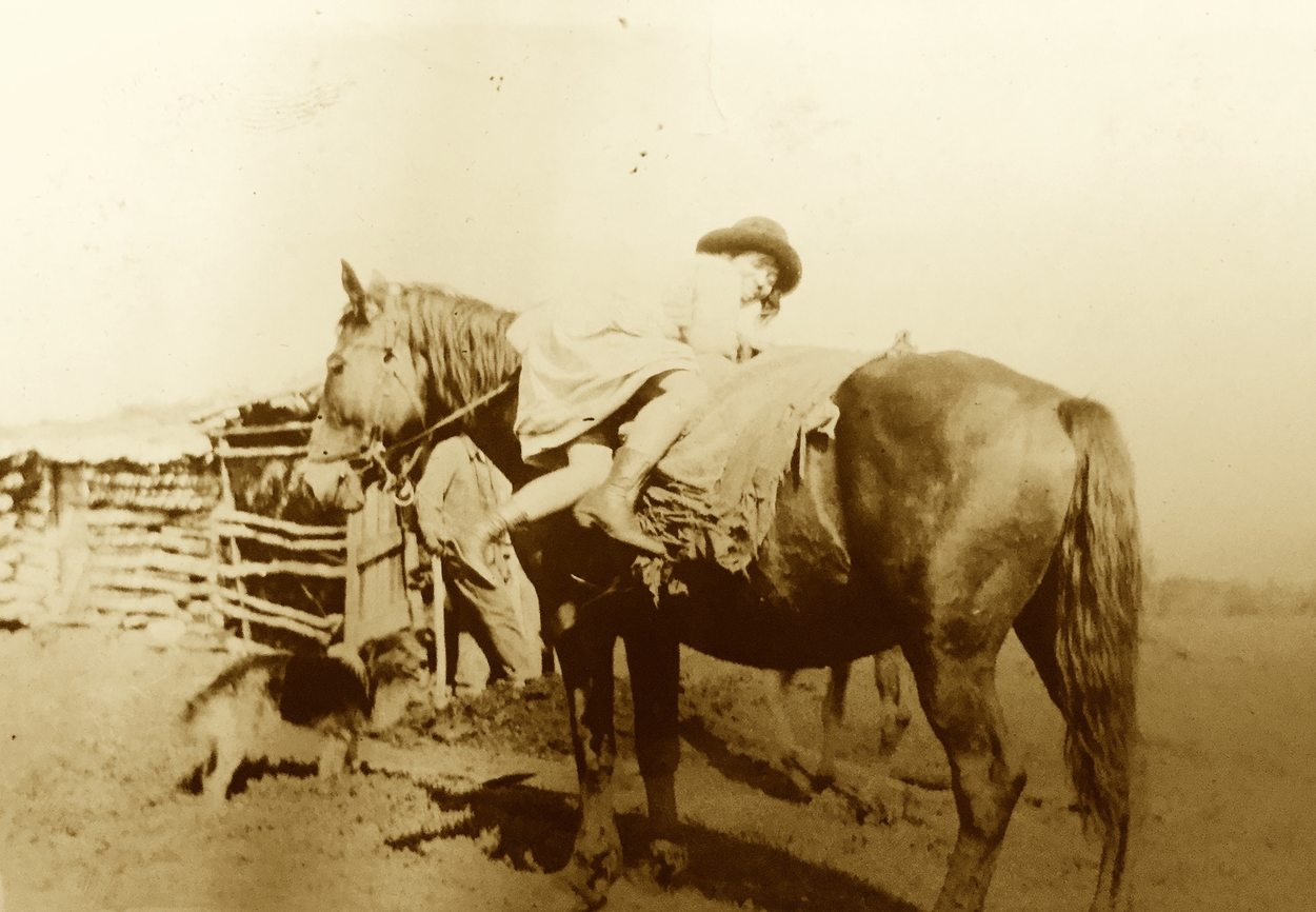 a woman wearing a hat and a dress climbs onto a horse