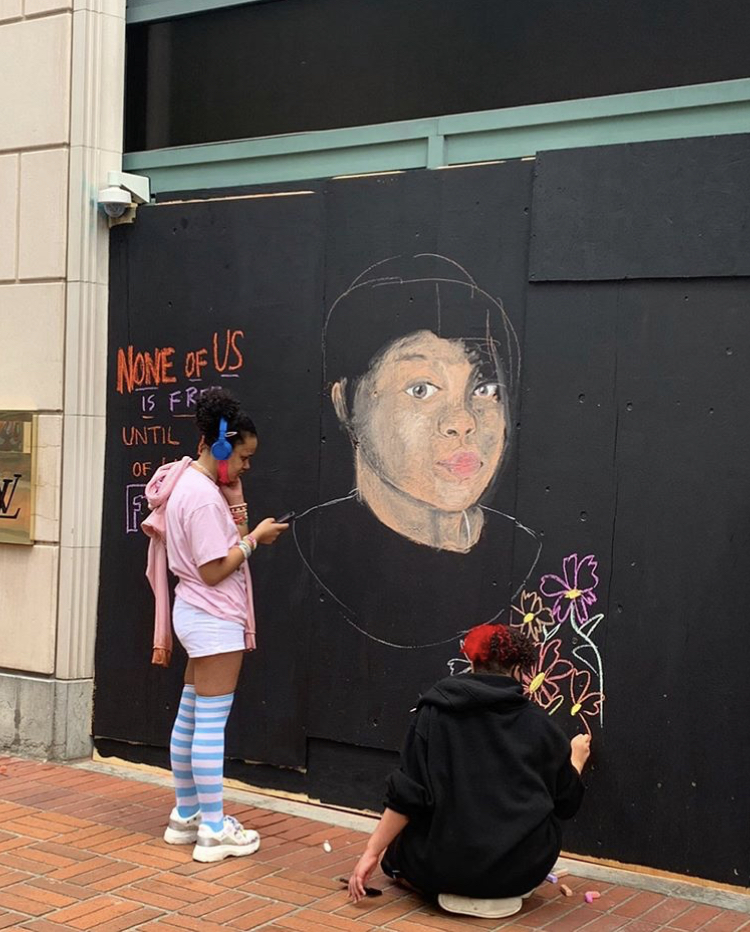 Two young teenagers work on a mural of Breonna Taylor in downtown Portland