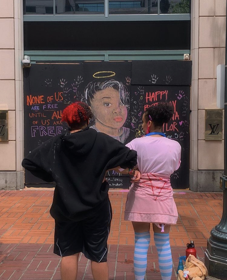 two siblings stand before the mural of Breonna Taylor they completed in downtown Portland